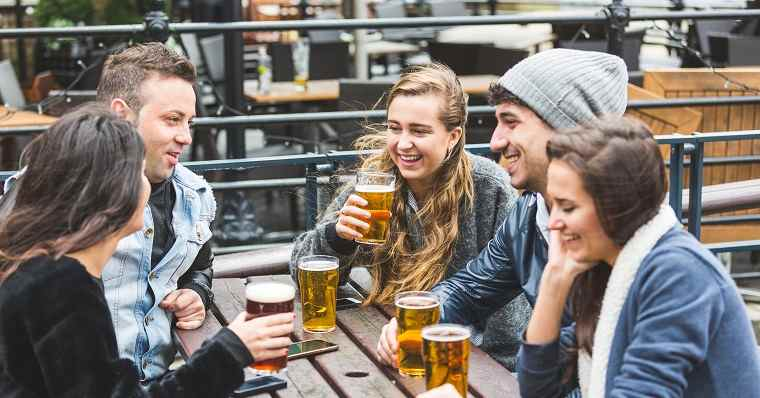 young-friends-drinking-beer-at-pub
